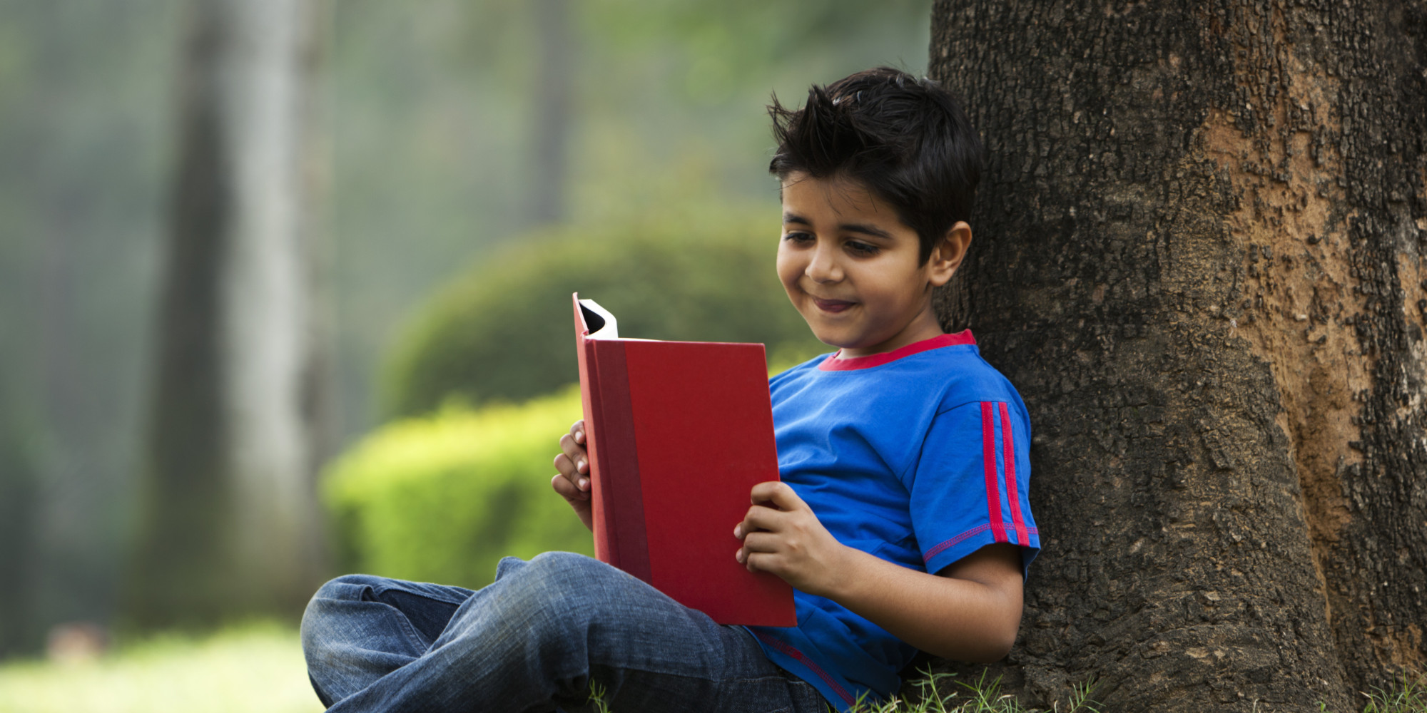 child-reading-under-tree